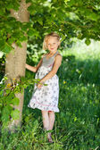 Beautiful little girl under a green tree — Stock Photo