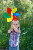 Small girl with a rainbow coloured windmill — Stock Photo