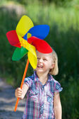 Smiling little girl with a colourful pinwheel — Stok fotoğraf