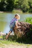 Little girl clambering onto a rock — Stock Photo