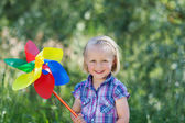 Happy little girl with a large pinwheel — Stock Photo