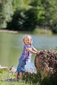 Cute little girl at the edge of a lake — Stock Photo