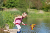 Young girl catching fish at the lake — Stock Photo