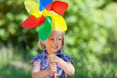 Linda garota jovem, com um moinho de vento colorido — Foto Stock