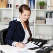 Businesswoman writing notes in the office — Stock Photo