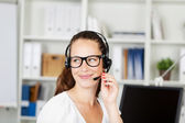 Smiling office worker wearing a headset — Stock Photo