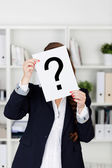 Office worker holding up a question mark — Stock Photo