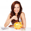 Young woman saving her change in a piggy bank — Stock Photo