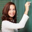 Smiling teacher writing on a blackboard — Stock Photo