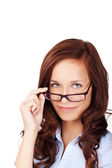 Beautiful woman peering over her glasses — Stock Photo