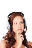 Thoughtful young woman listening to music — Stock Photo