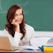 Attractive female student thinking as she studies — Stock Photo