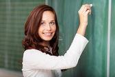 Smiling teacher writing on a blackboard — Stock Photo