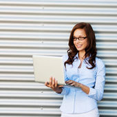 Woman standing and checking mails on laptop — Stock Photo