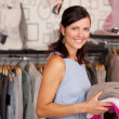 Smiling Woman Holding Stack Of Clothes In Boutique — Foto Stock