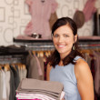 Saleswomen Holding Stack Of Clothes In Boutique — Stock Photo