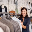 Smiling Woman Choosing Shirt In Clothing Store — Stock Photo