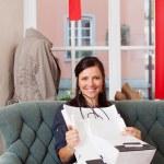 mujer feliz con bolsas sentado en el sofá en tienda de ropa — Foto de Stock