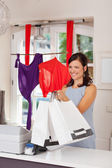Happy Saleswoman Giving Shopping Bags To Customer — Stock Photo