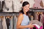 Smiling Woman Holding Stack Of Clothes In Boutique — Stock Photo