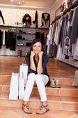 Mulher com sacolas e sapatos sentado nos degraus boutique — Fotografia Stock