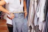 Kobieta próbuje niebieski do spodni w sklepie odzieżowym — Zdjęcie stockowe