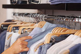 Womans Hand Selecting Shirt From Rack In Clothing Store — Stock Photo