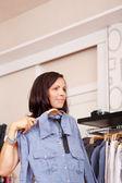 Kobieta stara koszulka patrząc od hotelu w sklepie odzieżowym — Zdjęcie stockowe