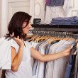 Customer Choosing Clothes From Rack In Clothing Store — Stock Photo