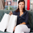Woman With Shopping Bags Sitting On Sofa At Clothing Store — Stock Photo
