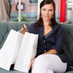 mujer con bolsas de compras, sentado en el sofá en tienda de ropa — Foto de Stock