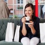 cliente tomando café mientras está sentado en el sofá en tienda de ropa — Foto de Stock
