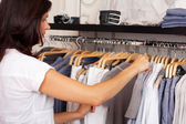 Woman Choosing Shirt From Rack In Clothing Store — Stock Photo