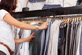 Woman Choosing Trouser From Rack In Clothing Store — Stock Photo