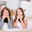 Two pretty young teenage girls laying on the floor — Stock Photo
