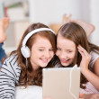 Two young girls share headphones to listen music — Stock Photo #26708903