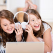 Two young girls share headphones to listen music — ストック写真