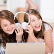 Two young girls share headphones to listen music — Stok fotoğraf