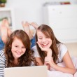 Two amused young teenage girls using a laptop — Stock Photo