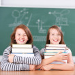 Schoolgirls embracing each a pile of books — Stock Photo