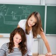 Two schoolgirls work together in a group work — Stock Photo
