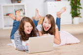 Two young teenage girls using a laptop laughing — Stock Photo