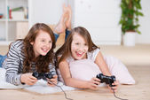 Two young girls happily playing video games — Stock Photo