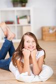 Happy young teenage girl laying on the floor — Stock Photo