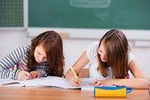 Alunas escrevendo em seus notebooks em classe — Foto Stock
