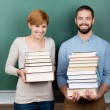 Teachers With Stack Of Books Against Chalkboard — Stock Photo #26739509