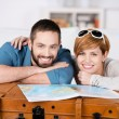 Couple With Map Leaning On Suitcase In House — Stock Photo #26740361