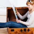 Woman Sitting In Suitcase While Looking At Map — Stockfoto