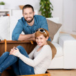 Young Couple With Briefcase In Living Room — Stock Photo