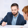 Explaining Documents To Female Co worker At Desk — Stock Photo #26744181